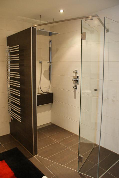 Handtuchheizkörper verchromt seitlich offen und geflieste Dusche.