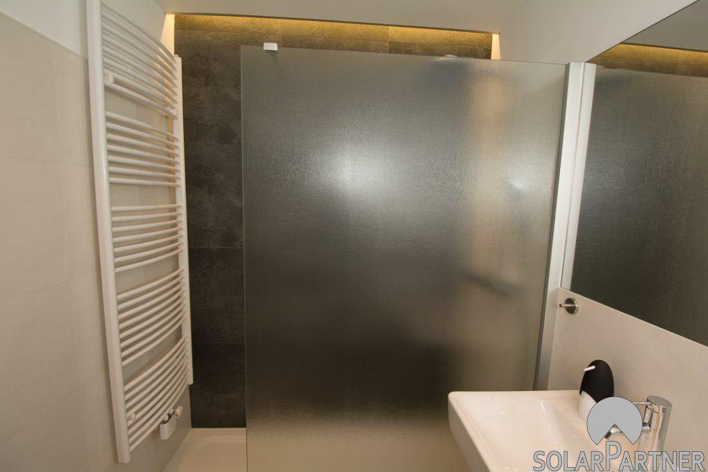 Walk-in-Dusche mit Glaswand und Handtuchheizkörper.