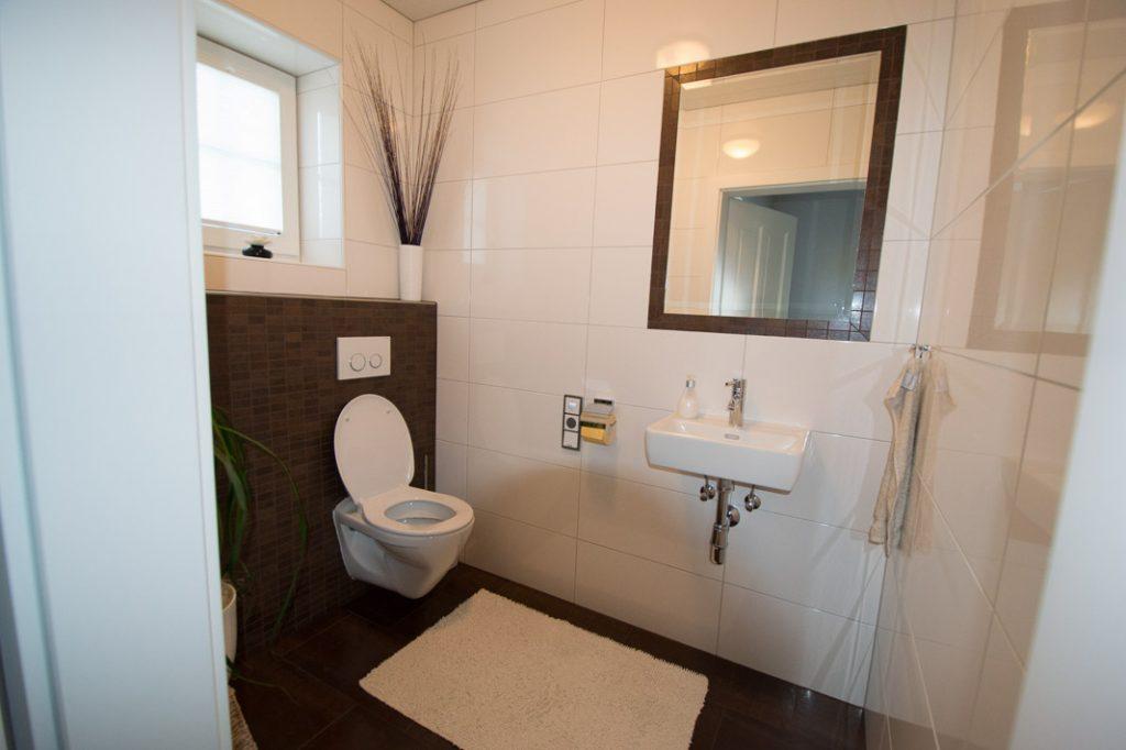Barrierefreies WC mit Handwaschbecken.