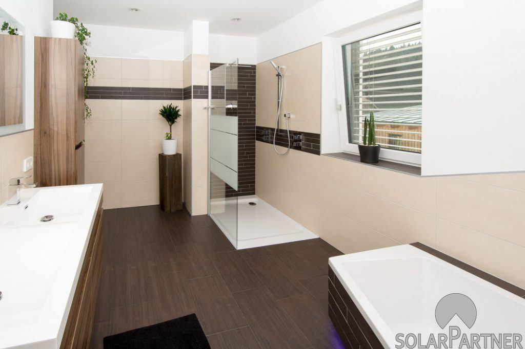 Walk-in-Dusche mit Glaswand samt Handtuchhalter.