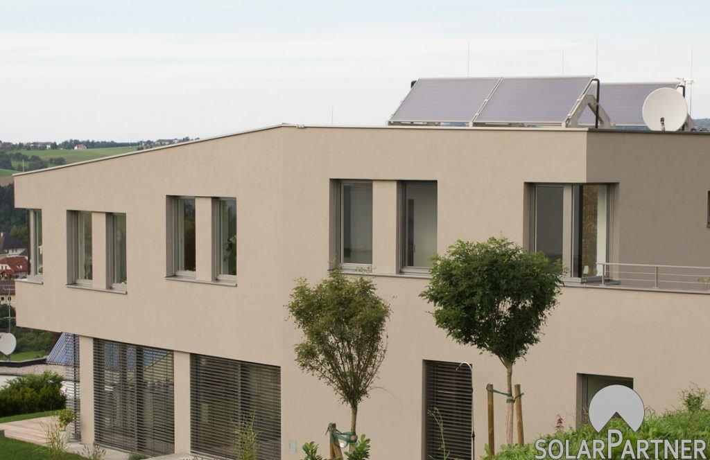 Thermische Solaranlage auf einem Wohngebäude mit Flachdach.